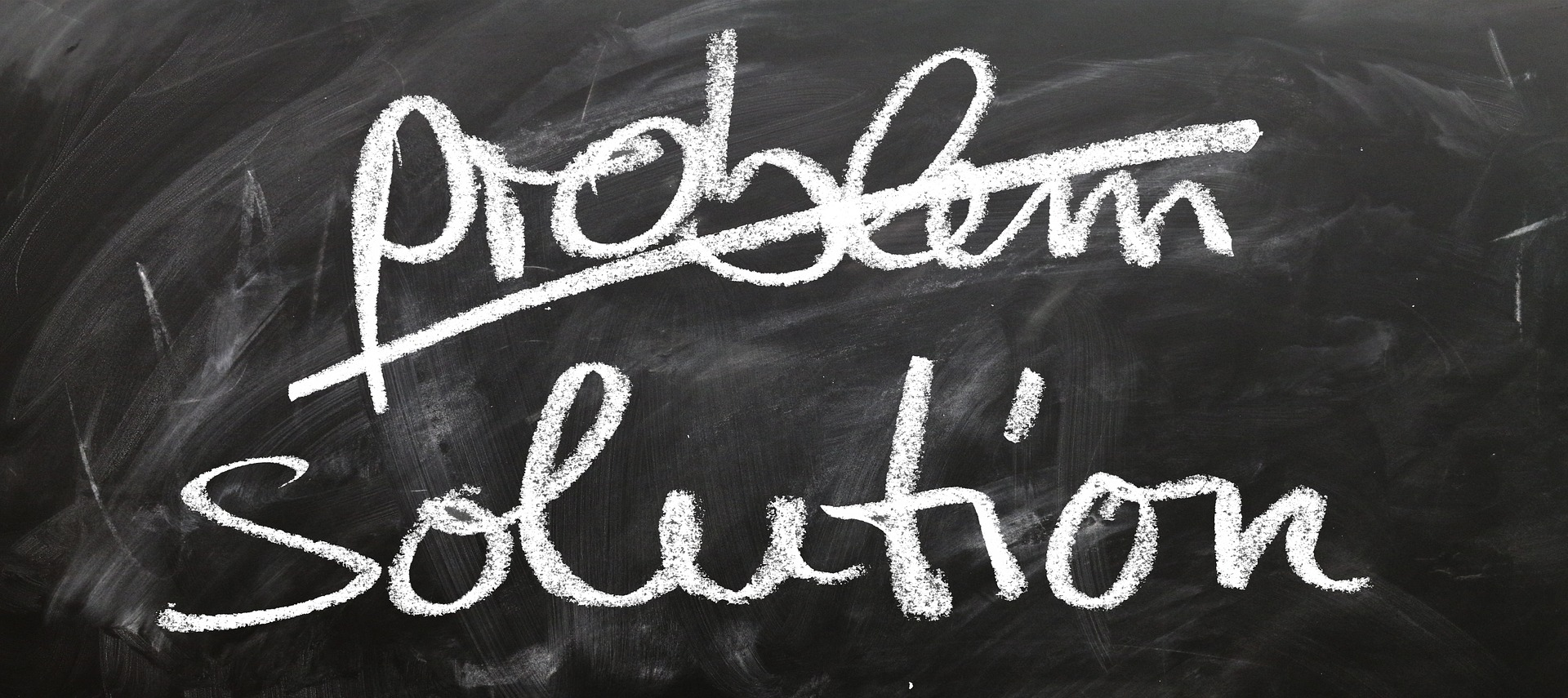 """A chalkboard with """"problem"""" crossed out and """"solution"""" written below it"""